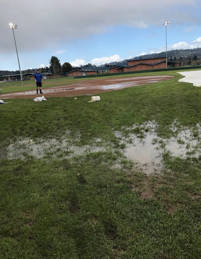 A+grounds+crew+member+surveys+the+field+conditions+at+Newberg+High+School+before+going+to+work.