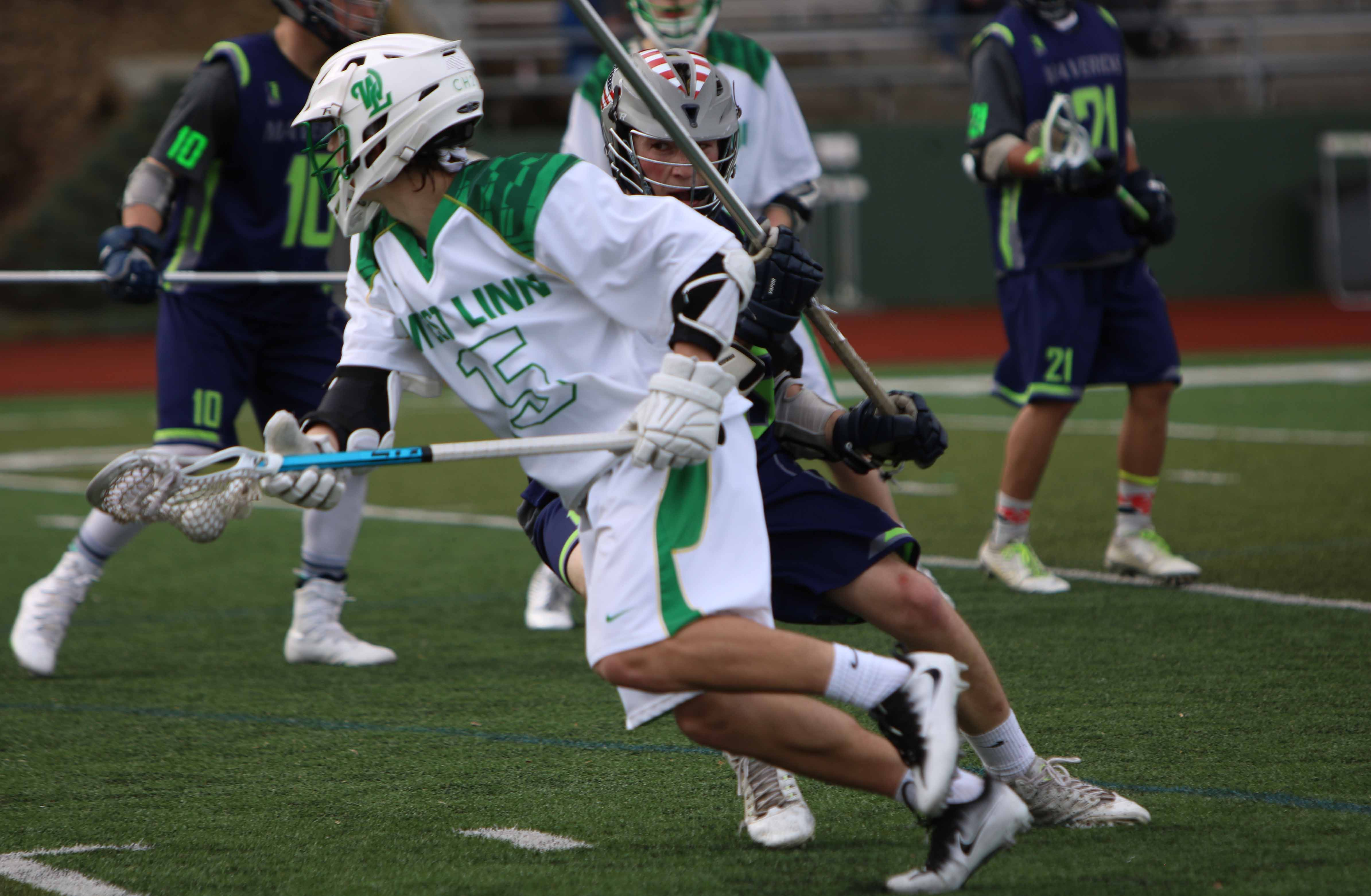 Dodging past defenders Ross Scott, sophmore attackman, looks up the field to teammates in 12-7 win against Oregon Episcopal School.
