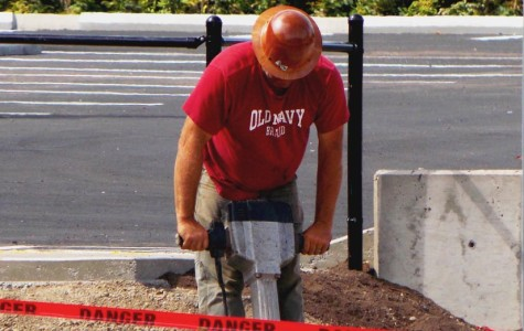 A construction worker uses a jack-hammer while finishing the senior parking lot construction. The lot is to be open on Tuesday to coincide with the first day of school for seniors according to Lou Bailey, prinicpal.