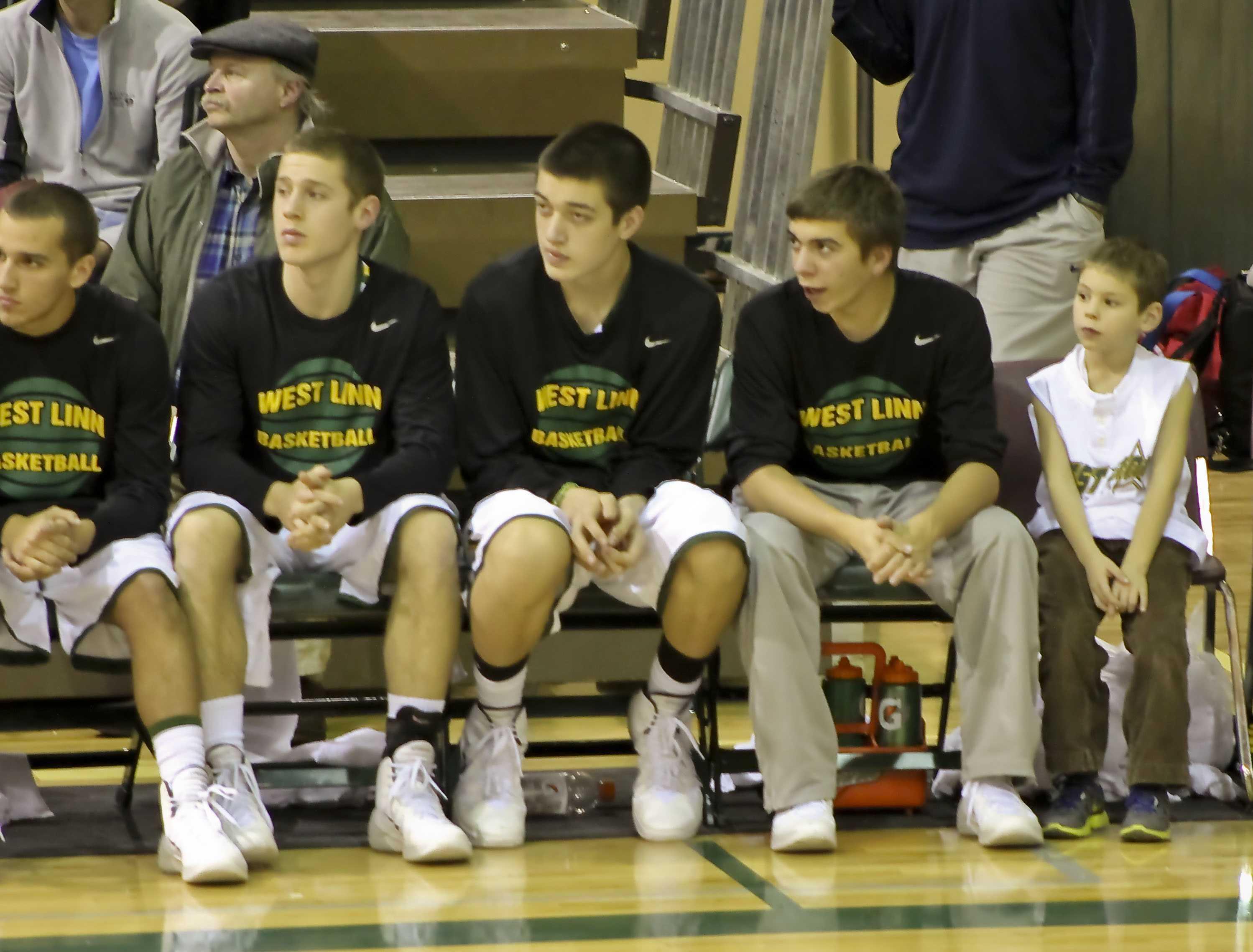 David Pulaski, junior, Matt Wright, senior, Colin Shearmire, sophomore, and  Manager Ben Baldwin, junior, watch as West Linn takes on Rival Oregon City.