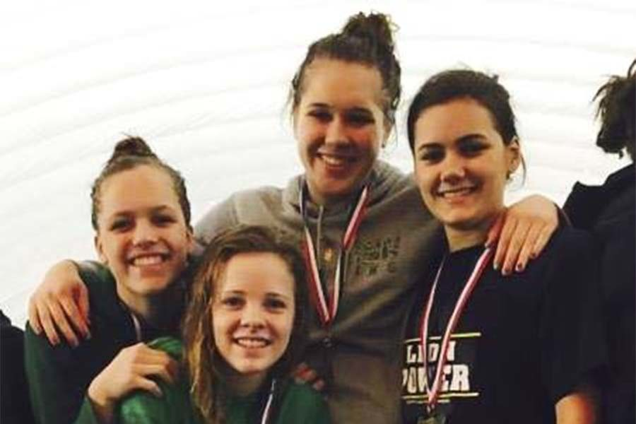 Robin Pinger, junior, Brianna Dyrdahl, senior, Laura Lauderoute, junior, Kylie Norris, junior stand on the podium after receiving their first place medals. The relay team took first in the 100 meter breaststroke at the state championship meet on Feb. 21.