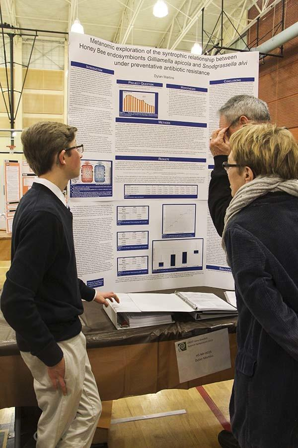 Dylan Martins, junior, explains his project to a visitor. His project was presented during the ISEF competition on Feb. 26.