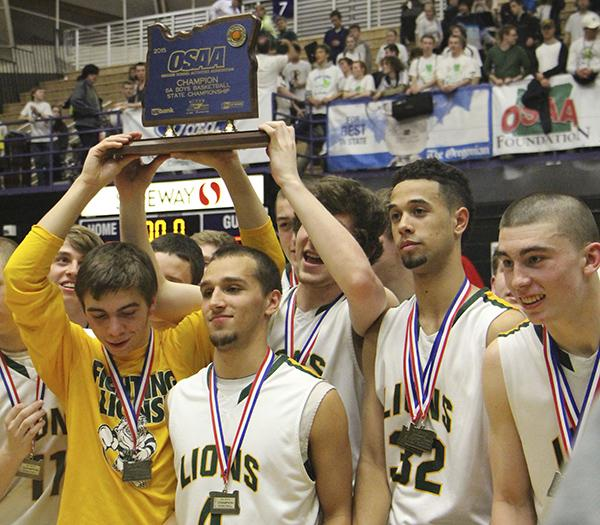 Pictured with their state championship trophy, the Lions have become the second team in Oregon Boy's Basketball history to win three consecutive state titles.
