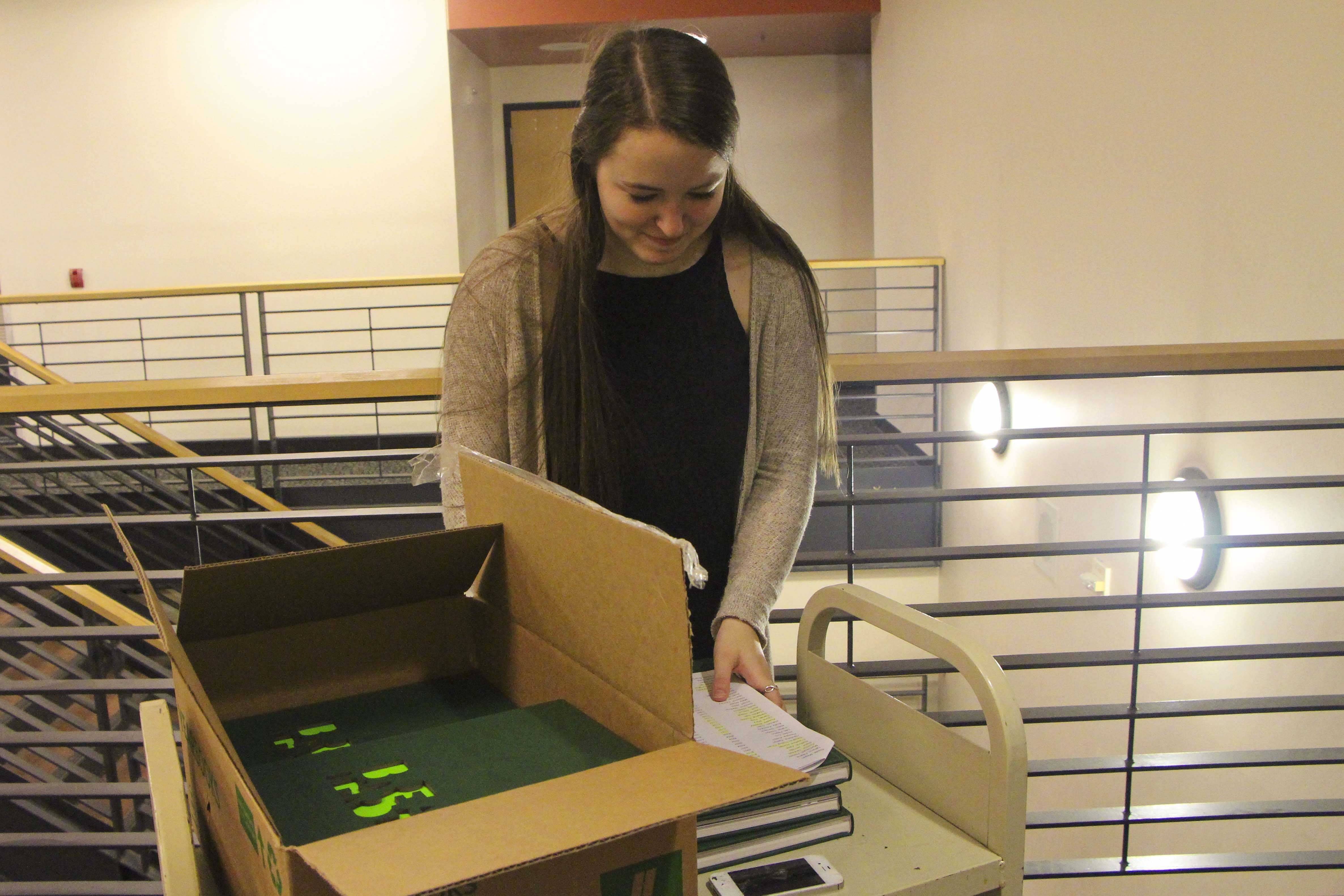 Jillian Emken, junior, hands Bryan Chapman, freshman, his yearbook. The 2015 Green and Gold yearbook is 220 full color pages and features a different design concept in each section.
