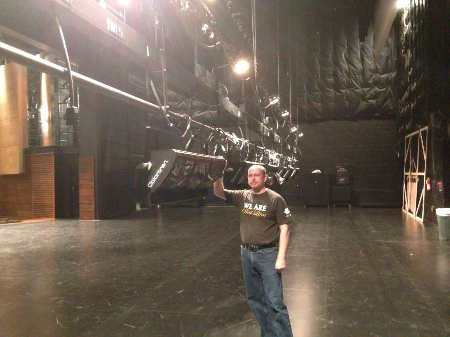 """Jon Ares, Performing Arts Technical Coordinator, is in charge of, among other things, maintaining the lights by """"flying them in"""": lowering them into reach. He posed for this picture while giving a tour of the backstage area."""