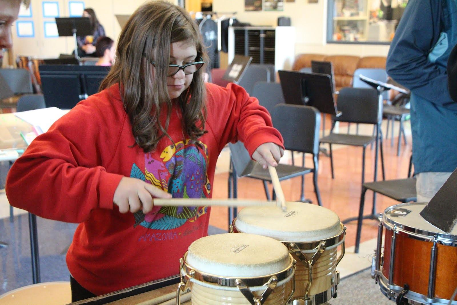 Playing the bongos during the first unified band lesson, Emma Harris, junior, learns the basics of playing music. Harris is a participant of the unified band that meets on Thursdays after school.
