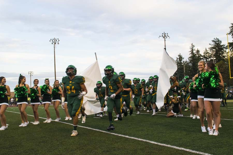 Boys Varsity Football Players bursts through the banner; prepared to keep the winning streak going in one of the first home games.
