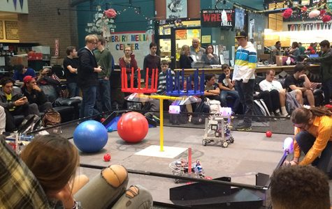 Robotics teams show students the final product of coding by working with their robots in the library during lunch.
