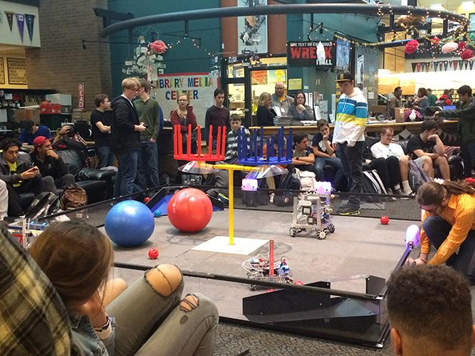 Robotics+teams+show+students+the+final+product+of+coding+by+working+with+their+robots+in+the+library+during+lunch.