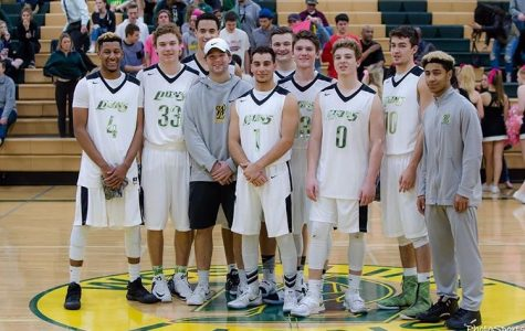 Graduating basketball players pose at mid court after a 92-74 win on senior night.