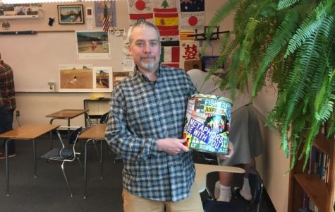 """Mr West, English teacher, with the Thought Pot. During the week, students could put their original stories and drawings into the Pot, and Mr. West would read them to the class every other Friday. """"The senior class voted on the Teacher of the Year,"""" Mr. West said. """"I won twice. Both times they took a photo of me with the Thought Pot for the yearbook. That was my thing. But that thing is gone."""""""