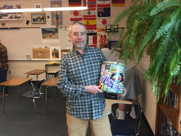 "Mr West, English teacher, with the Thought Pot. During the week, students could put their original stories and drawings into the Pot, and Mr. West would read them to the class every other Friday. ""The senior class voted on the Teacher of the Year,"" Mr. West said. ""I won twice. Both times they took a photo of me with the Thought Pot for the yearbook. That was my thing. But that thing is gone."""