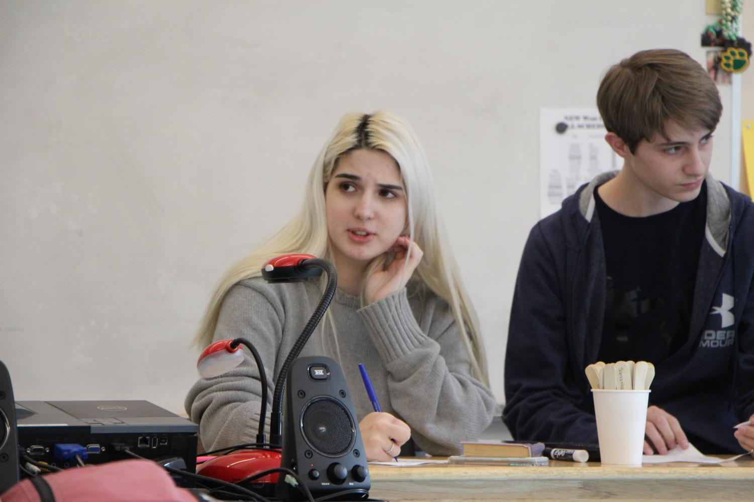 Members of the speech and debate team, Cynthia Medhaug-Aversano, junior, and Haydn Maust, freshman, run through their arguments during a speech and debate meeting. Although they didn't advance to the state competition, three of their teammates did.