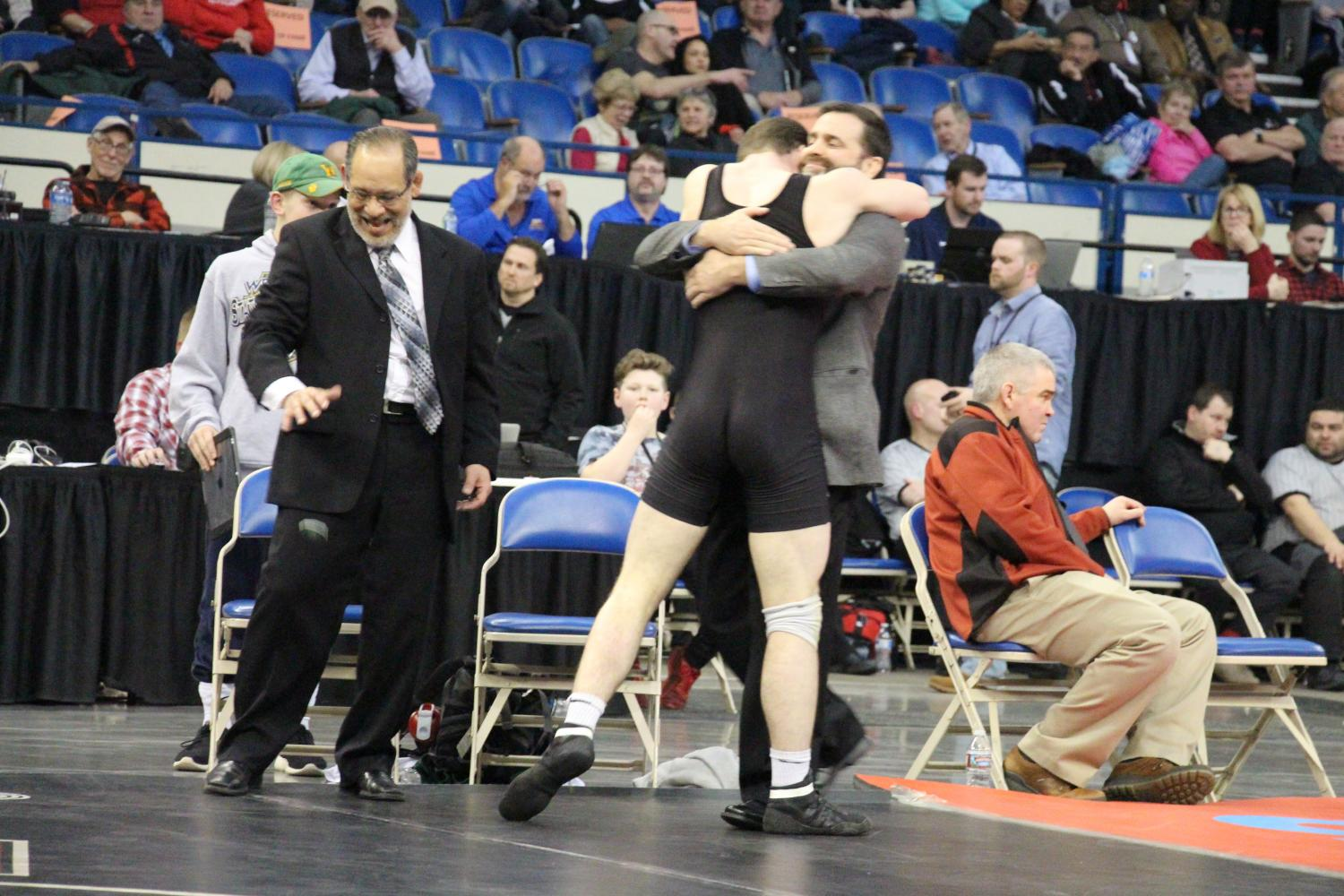 Celebrating after a pin with his father and head coach for his first ever state title, sophomore Sean Harman is overcome with emotion as he looks towards the crowd. Sean's title came in the class 6A 152 pound weight class, and he is only the second Harman ever to win a wrestling state championship.