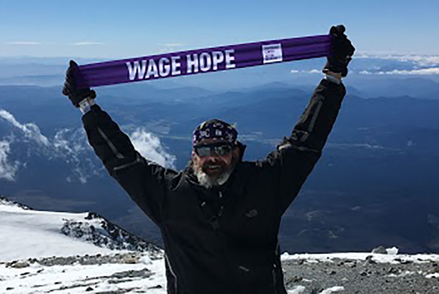 Joe Heiden at the top of Mount Adams holding a wage hope banner. Heiden brings a wage hope banner with him everytime he does something noteworthy or mentionable. He appeared on several talk shows in Portland after his appearance on American Ninja Warrior, and at these interviews he held up the wage hope banner to bring awareness to pancreatic cancer.