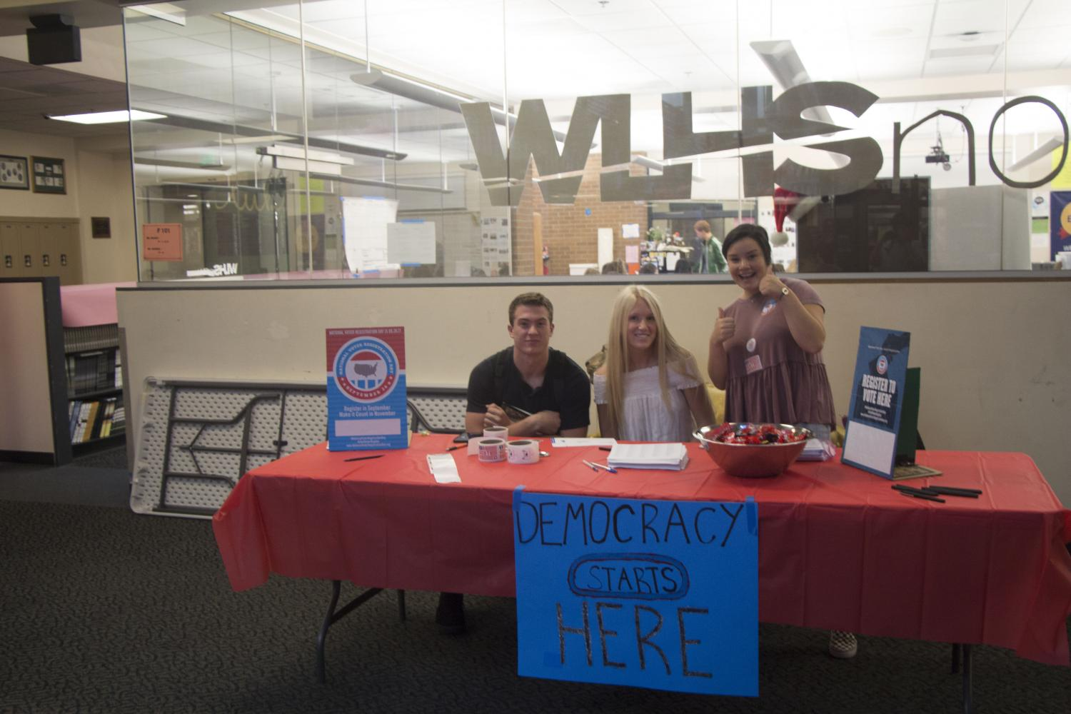 Students working with the Bus Project, armed with stickers and candy, await eager voters-to-be. From left to right: Zack Huffstutter, senior; Haley Thayer, senior; Skylar Kool, senior.