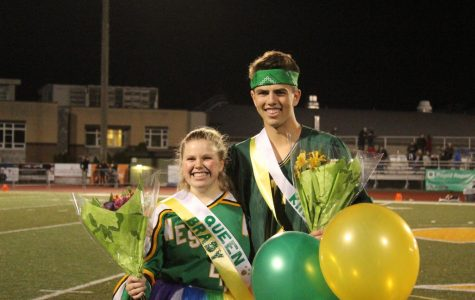 """King Dylan Tiffany and Queen Brady McDevitt smile at the roaring crowd. For decades, there was only a queen and princesses. The second annual homecoming queen was Queen Anita Nunn in 1954. Starting in 1958 there were male escorts. It wasn't until 1986 that there was a King and Queen. """"I didn't think I was going to be queen, I looked right at Dylan before, and said it's not going to be us,"""" Brady McDevitt said, """"and then they opened the box, and I saw the balloons, and I looked down and I said 'Oh, nobody else has balloons,' so it was pretty cool."""" Instead of crowns, balloons determine the winners. The first homecoming queens didn't have crowns either. Crowns were not a part of homecoming until 1961 and these crowns were very small and almost tiara like, with a lot of sparkles."""
