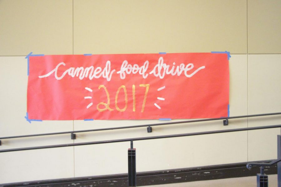 Welcoming students inside the school: avibrant sign advertising the canned food drive.