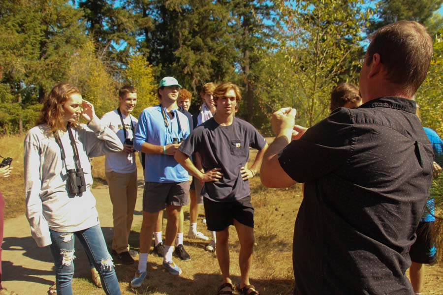 On a shuttle field trip to Browns Ferry Park in Tualatin, the AP Environmental Science class learns about native plants. Jim Hartmann, AP Envi Sci teacher, hold up a plant the students are trying to identify. The class is in a plant and bird identification unit and takes to the outdoors to learn plant and bird names.