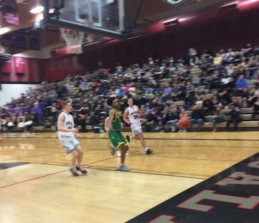Micah Garrett tracks down a loose ball versus Tualatin on Feb. 9. Garrett scored 18 points in the game. (Photo by Rory Bialostosky)