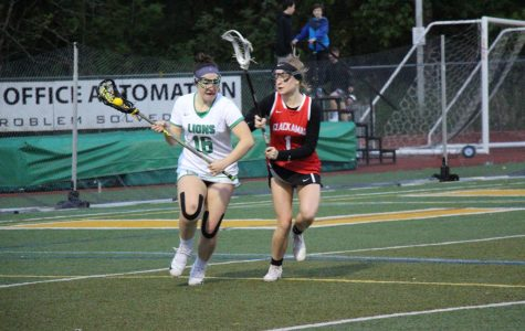 After getting the ground ball, senior Abby Manley makes her way up the field past Clackamas attackman.