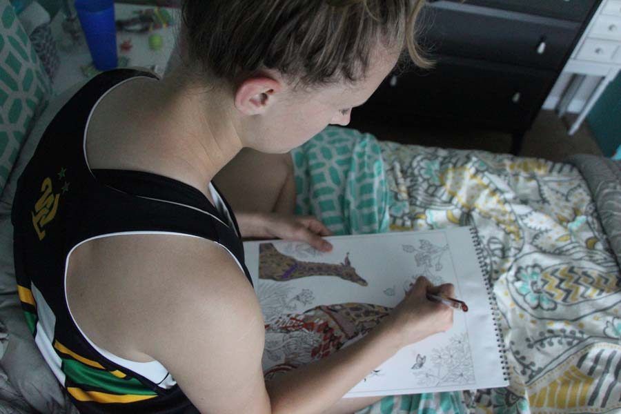 """Art Therapy Coloring in her therapeutic artbook Grace Jackson, sophomore is sitting in her bedroom with all her lights off to recover from the concussion.  """"I had to sit in the dark for 6 hours and just color without any electronics or TV!"""" Jackson said."""