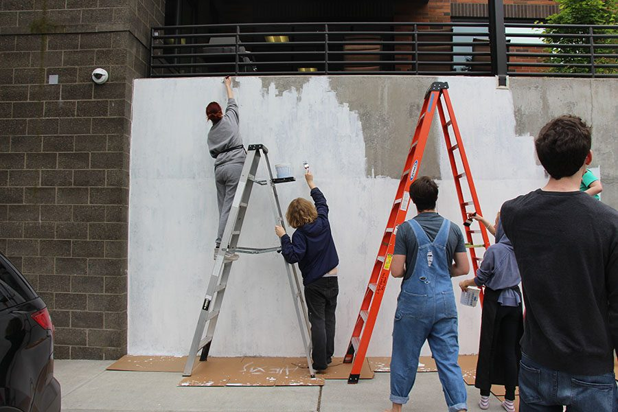 Students including Brice Brown and Alexis Mooney paint primer over the cement wall the mural will cover.