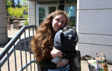 """Spending time in the sun during """"Baby Week"""", a health class tradition, Kendall Gordon, senior, holds her baby named Jeffers.  """"The baby assignment is actually a smaller assignment within a bigger, family planning project,""""  Kayeleigh Owens, health class teacher, said. """"So its a 3 week project that students in child development do, where they learn to have a career, from that career they get a budget, they budget for a month of family planning.""""  The baby project is a branch of the family planning project where students take care of a baby, which can be anything from a teddy bear to a doll, for five days at school and at home. The assignment began on April 23.  """"You have to record everything you do for 3 days of those 5 days,"""" Gordon said, """"and Ms. Owens has everybody watching around the school, so you can't slack off."""""""