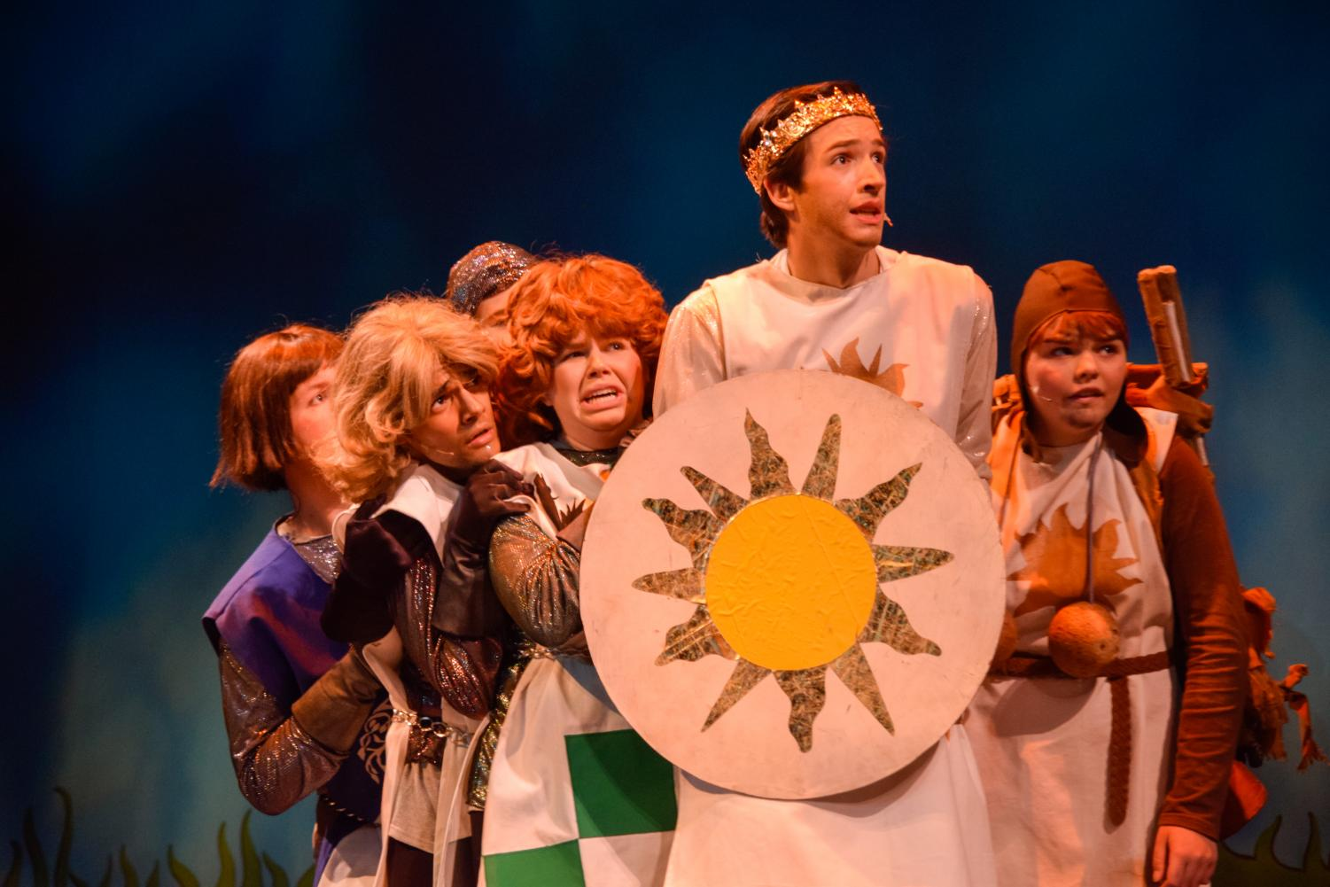 The knights of the round table: Cameron Masse, Matthew Snyder, and Brady McDevitt, hide behind the shield of King Arthur, played by Matt Lewis, with his trusty servant, played by Susie Walters.