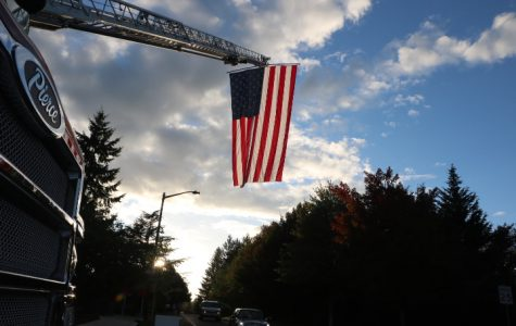The firefighters of station 55 raise an American flag 	over Hidden springs road.