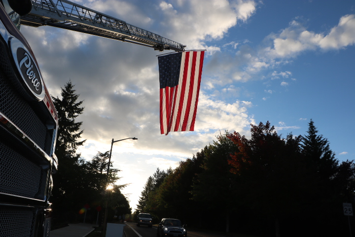 The+firefighters+of+station+55+raise+an+American+flag+%09over+Hidden+springs+road.+