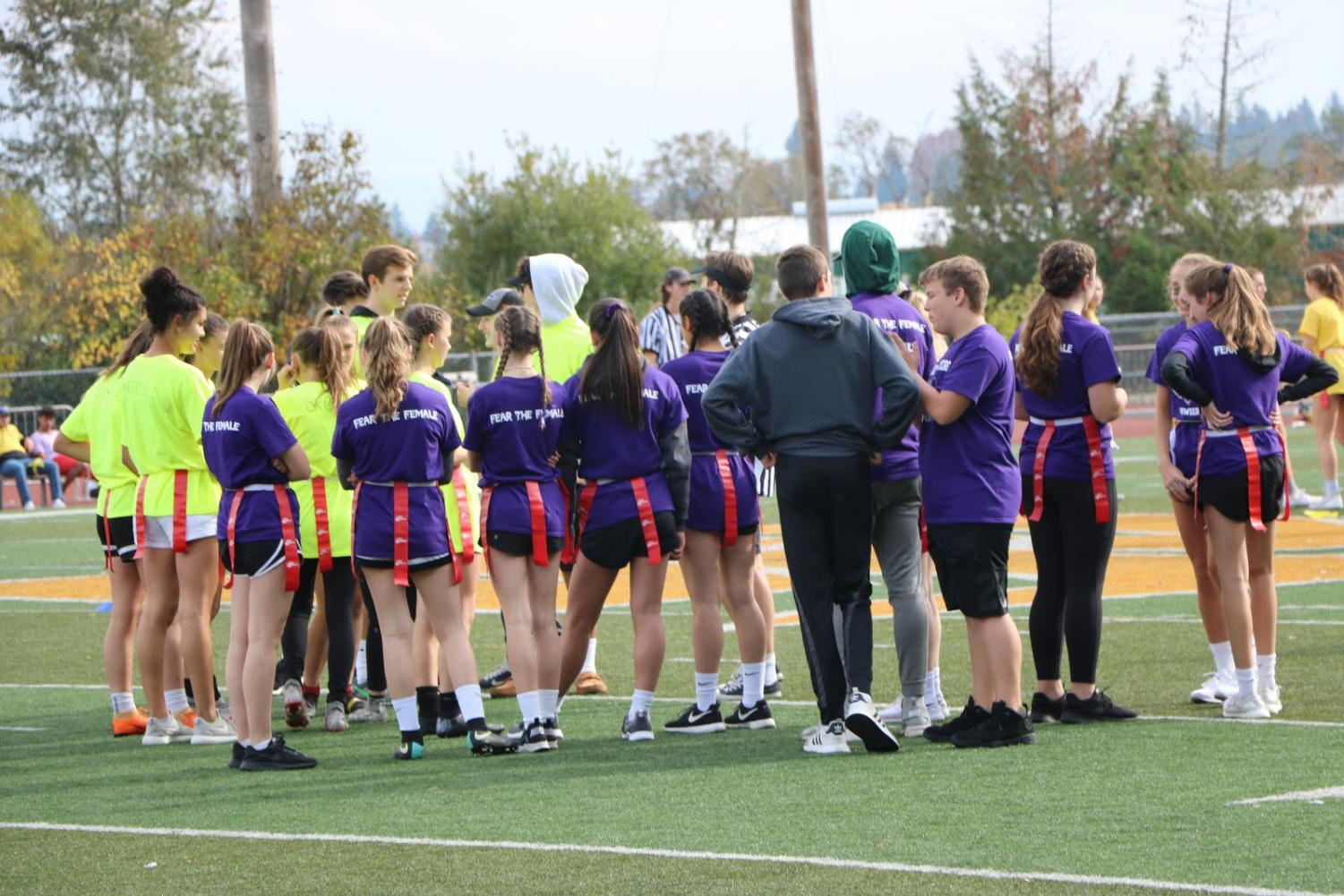 Team+Purple+and+team+Neon+Green+waiting+to+start+their+game.+The+coaches+can+be+seen+in+the+background%2C+discussing+technicalities.