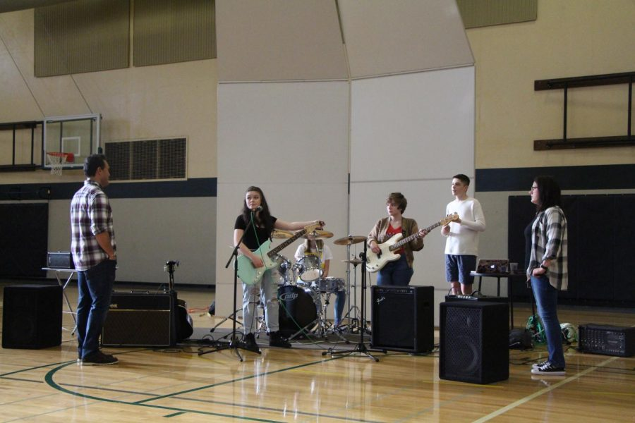 Before+the+homecoming+carnival%27s+first+ever+live+music+performance%2C+Ethan+Arterberry%2C+junior%2C+helps+student+band+Love+Circle+practice+for+their+later+performance.+Musicians+arrived+early+at+the+auxiliary+gym+to+rehearse+and+made+sure+the+event+would+go+smoothly.+%E2%80%9CI+was+nervous%2C%E2%80%9D+member+of+Love+Circle+and+junior+Gillian+McMahon+said.+%E2%80%9CI+perform+all+the+time+at+big+festivals+and+venues+all+over+Portland%2C+but+the+stakes+are+low+because+I+don%E2%80%99t+know+anyone.+I+knew+everyone+there%2C+and+I+just+didn%E2%80%99t+want+to+screw+up.%E2%80%9D
