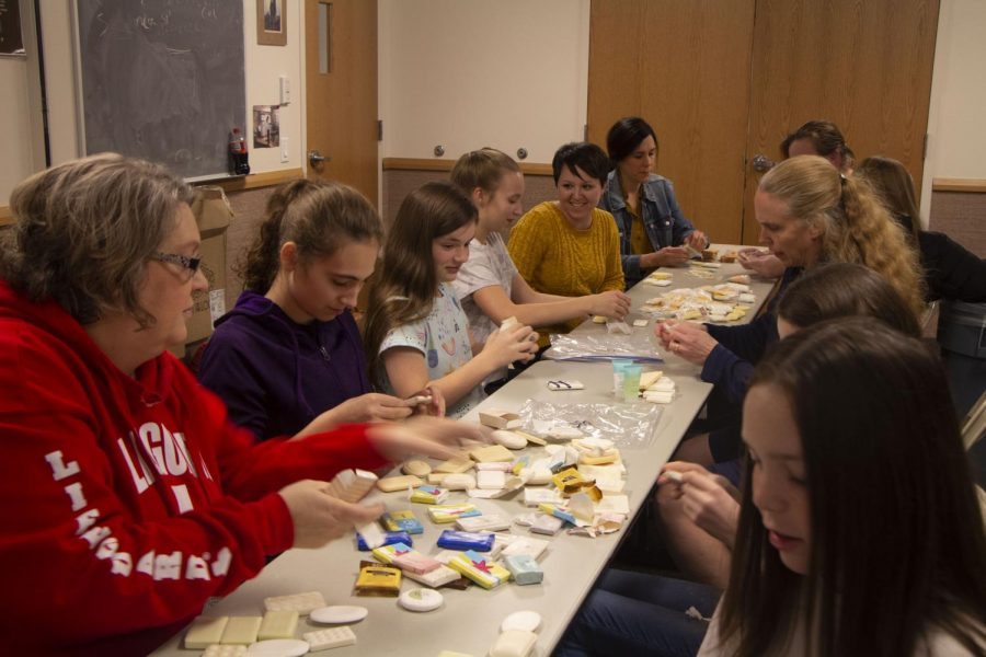 The Church of Latter-day Saints' beehive group and advisors remove plastic wrapping from bars of soap to be sent to young women in foreign countries.