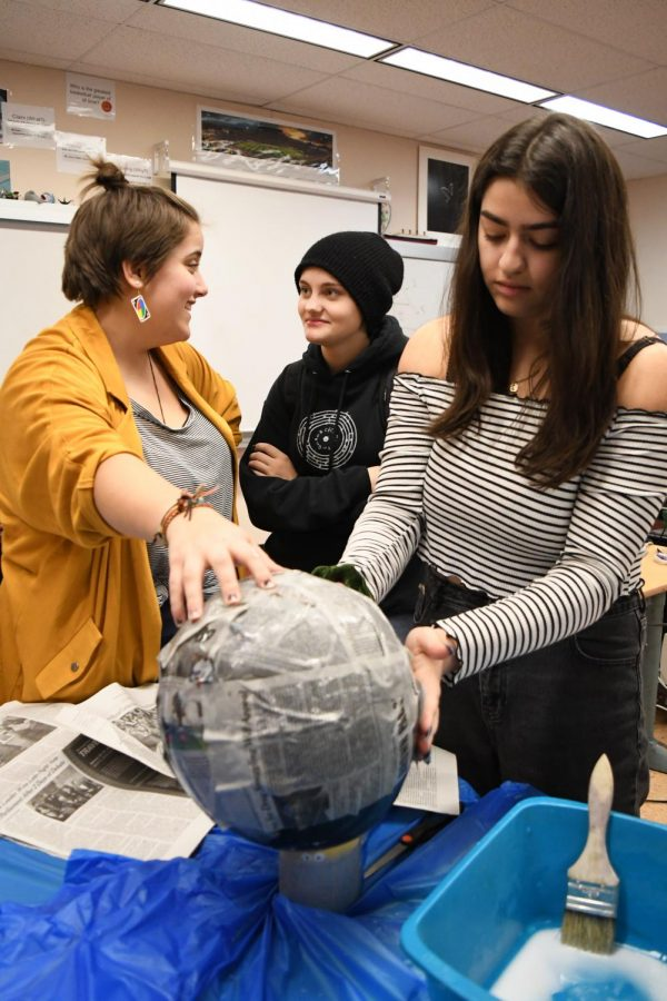 Fingers stretched to preserve palms from sticky glue, club founder Morgan Misra lays paper mache on model planets.