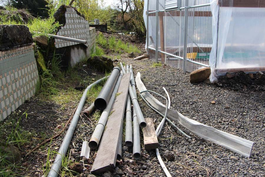 Leftover metal poles, and some remains from the old shed sit between the two greenhouses