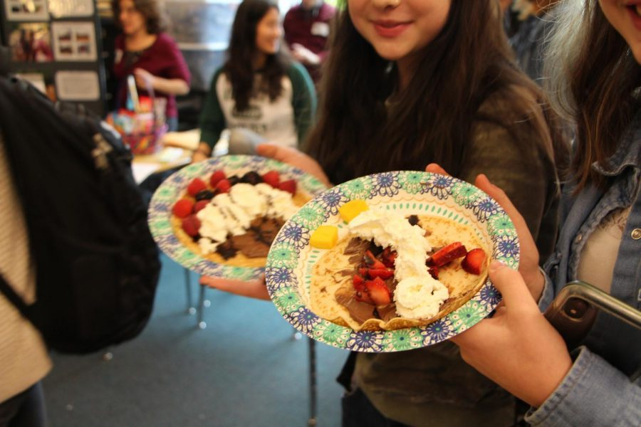 After carefully creating their crepes, Emily Newbore, freshman, and Aubrey Cutler, freshman, show off their creations.