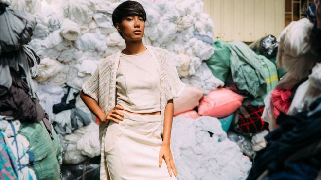 Ironic beauty; a model poses in front of textile waste, in a Cambodian factory.
