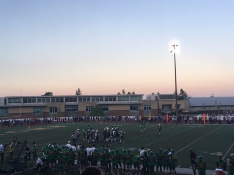 The sun sets over the football field as the Lions line up for a play in the first quarter.