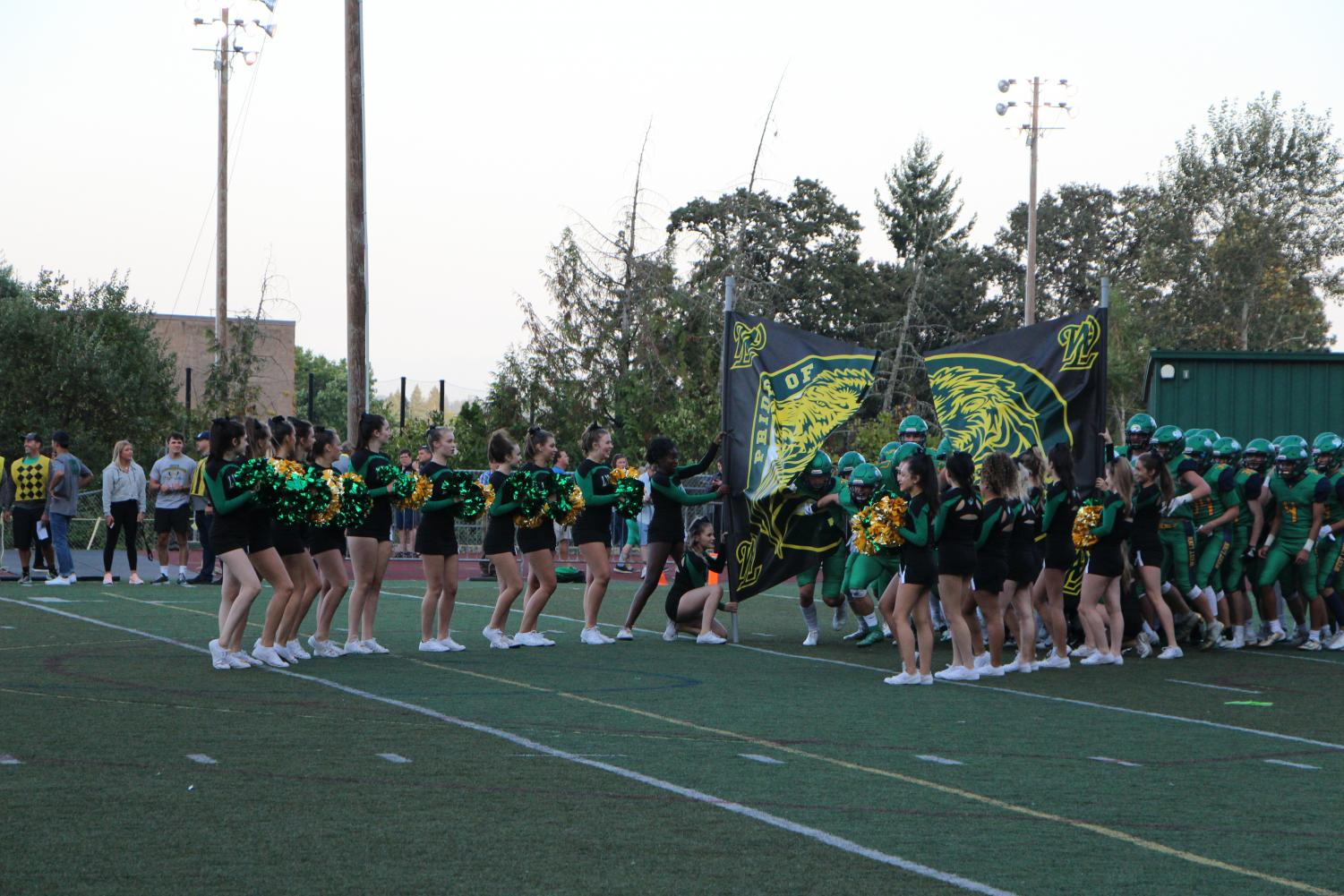 Players break through the  West Linn banner to start the game.