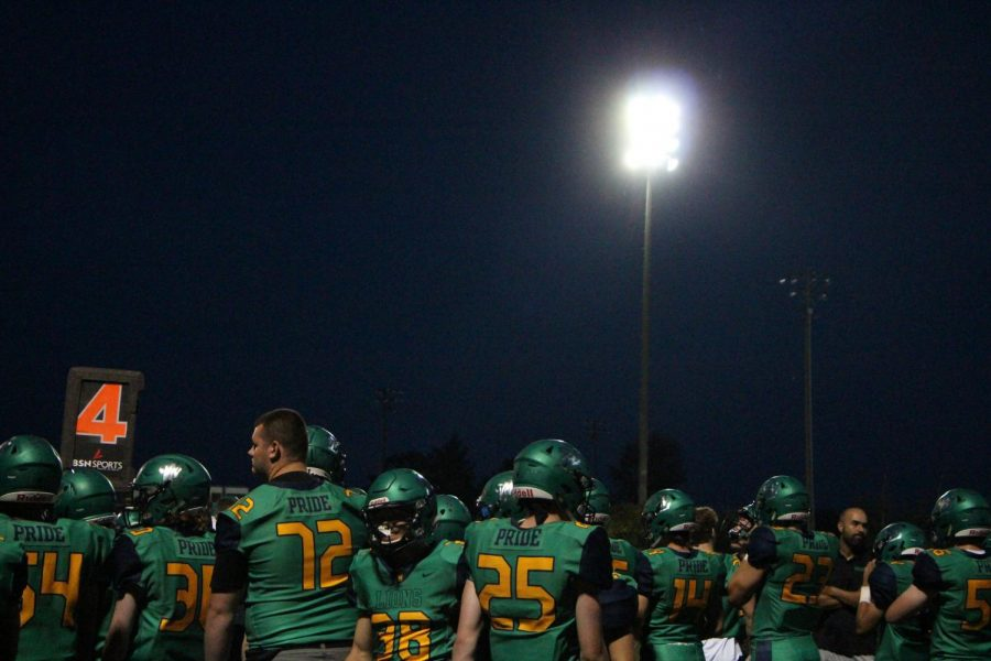 Players watch from the sideline as the second half begins.