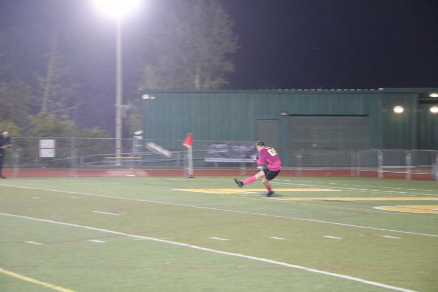 Watch it fly: winding up for a powerful kick, Caden Kesselring, junior, sends the soccer ball flying back to the opposing team, Tigard, as half time quickly approaches.