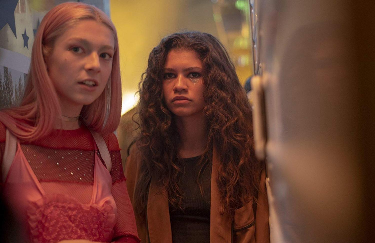 Rue, played by Zendaya Coleman, and Jules, played by Hunter Schafer, hide in-between carts at the town carnvial.