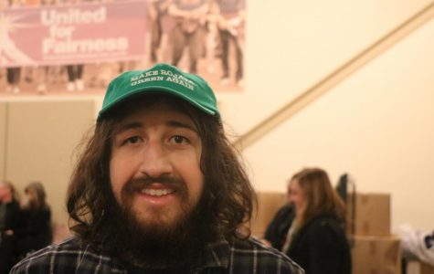 """Christopher Luchini wears a hat saying """"Make Rojava Green Again"""". Referring to a movement that is working towards a healthier climate and also supports the revolution taking place in Rojava (The Autonomous Administration of North and East Syria)."""