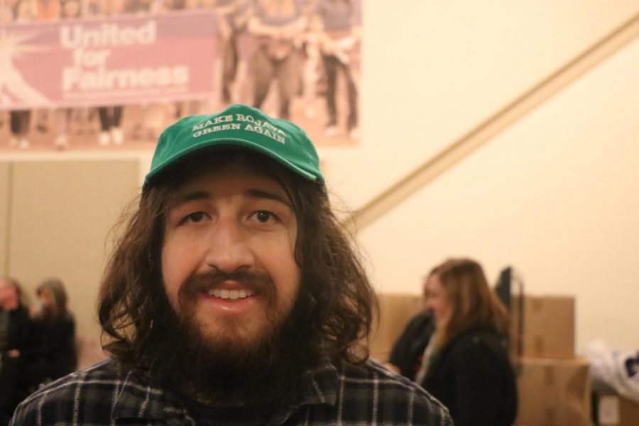 "Christopher Luchini wears a hat saying ""Make Rojava Green Again"". Referring to a movement that is working towards a healthier climate and also supports the revolution taking place in Rojava (The Autonomous Administration of North and East Syria)."