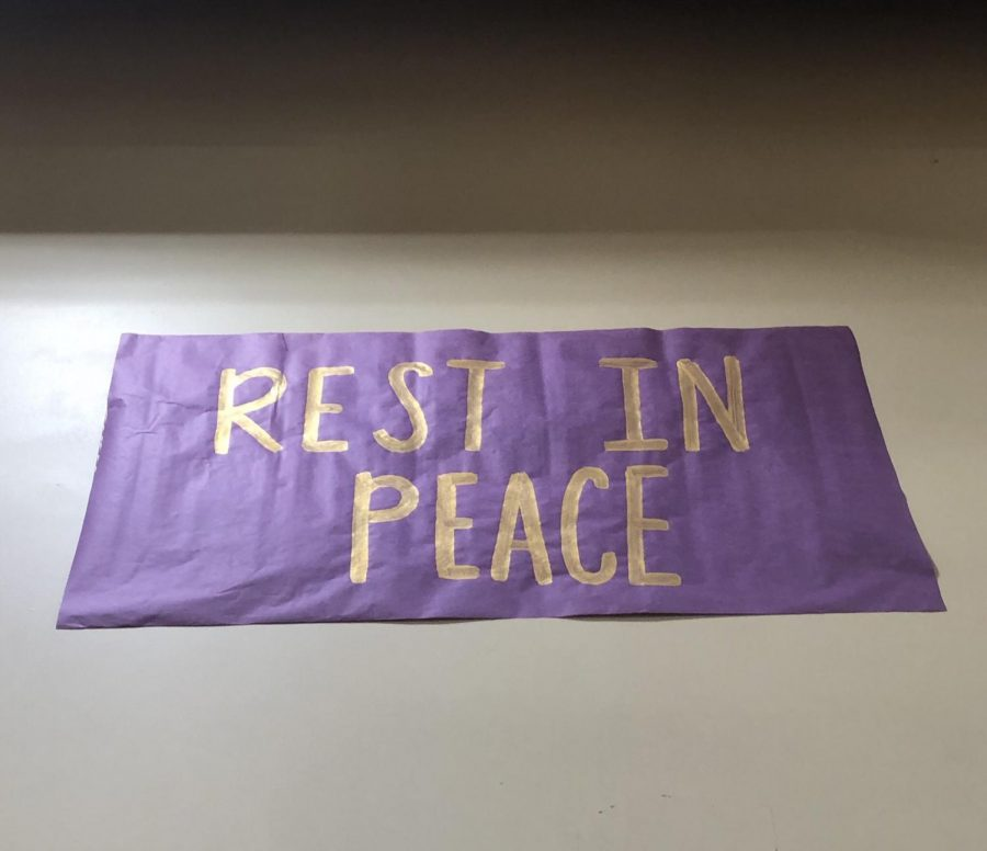 A purple and gold poster hanging in the gym for those who lost their lives during the helicopter crash.