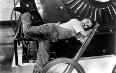 Posing for a photoshoot to advertise his film, Charlie Caplin leans over a lever.